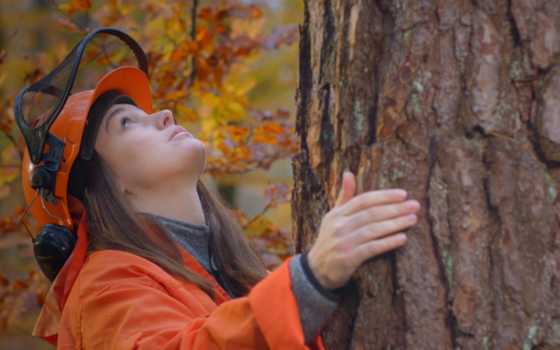 Kvinna i arbetskläder kramar en trädstam