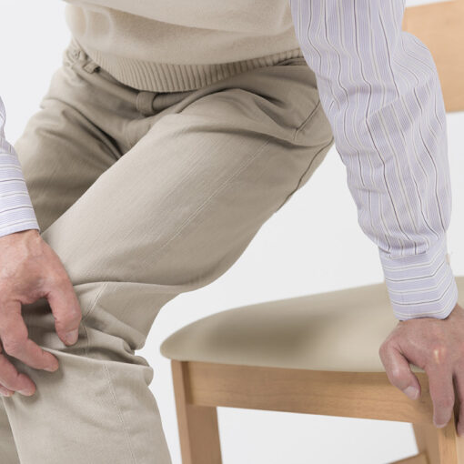Man med smärta som reser sig från en stol