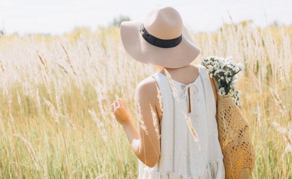 Sommarklädd kvinna som går i ett vetefält